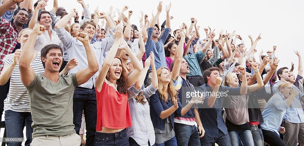 People standing in bleachers cheering