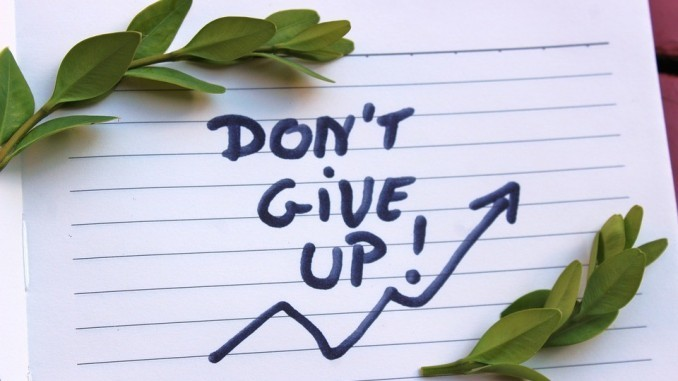 """A notebook page with the words """"Don't give up"""" and an upwards arrow written on it"""