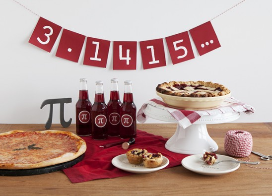 "Pizza, pie, and sodas in front of a banner that has ""3.1415..."" on it"