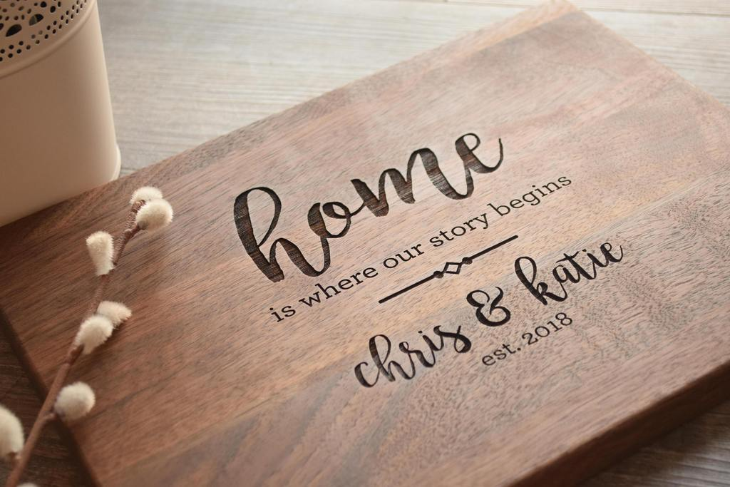 "A piece of wood that has ""home is where our story begins"" on it"